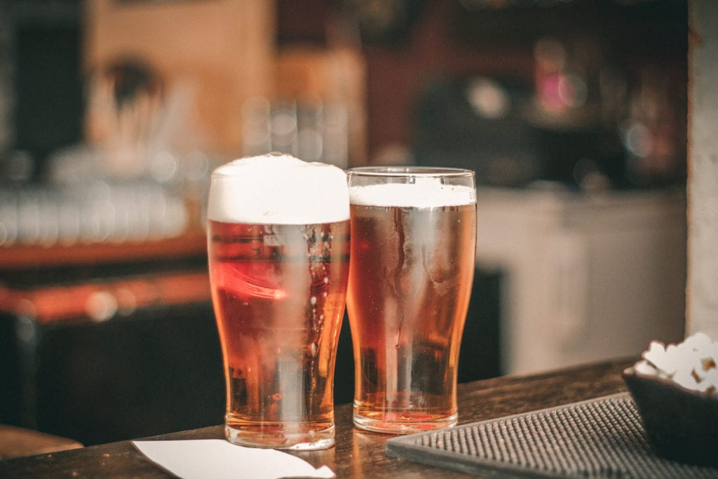 a picture of two pint glasses filled with beer.
