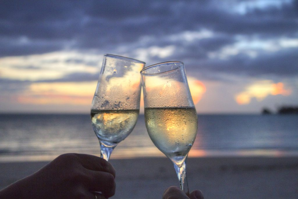 a picture of two glasses of white wine against a sunset backdrop.