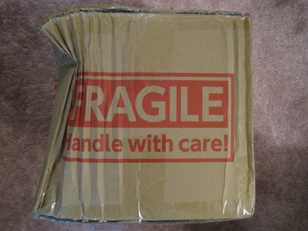 A picture of a heavily damaged package labeled fragile - handle with care to signify proper order fulfillment needs to consider damage in transit.