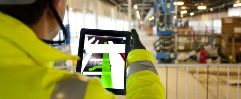 a picture of an industry worker holding a tablet device that displays an augmented picture of the plant floor.
