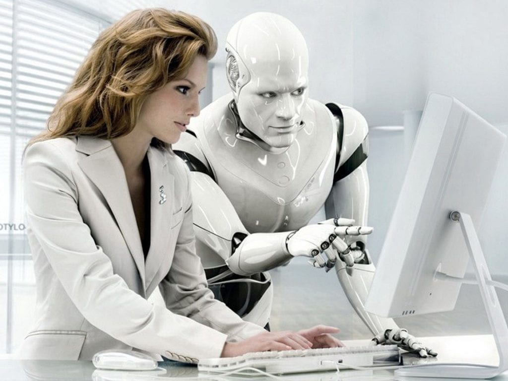 a photo of a Chief Robotics Officer and a robot discussing information on a computer monitor