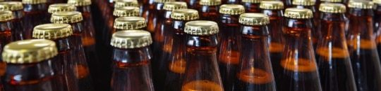 a photo of glass beer bottles on a bottling line in a food and beverage manufacturing brewery - encompass solutions.