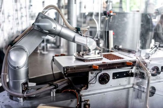 a photo of a robot in a food and beverage manufacturing facility where chocolate is made.