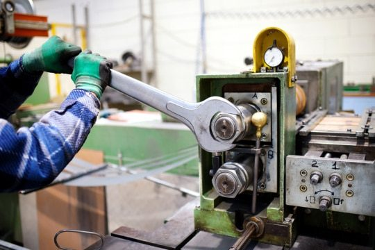 An image of a factory maintenance worker adjusting a machine as part of IIoT connectivity.