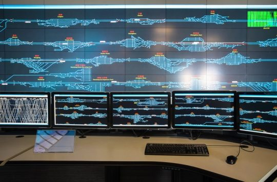 An image of a railway control room with monitors displaying a full rail system as part of IIoT connectivity.