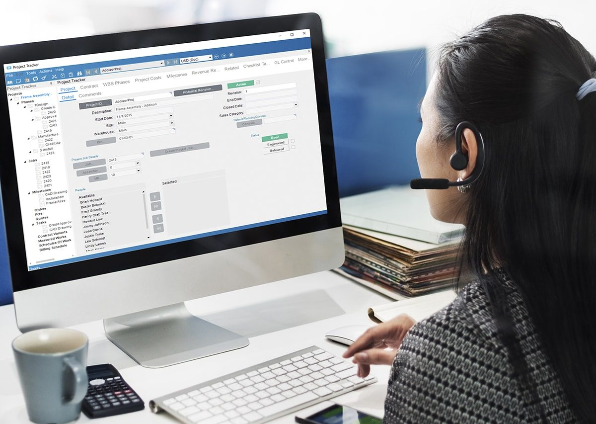 an image of an employee using enterprise resource planning software to track and schedule projects from her desk