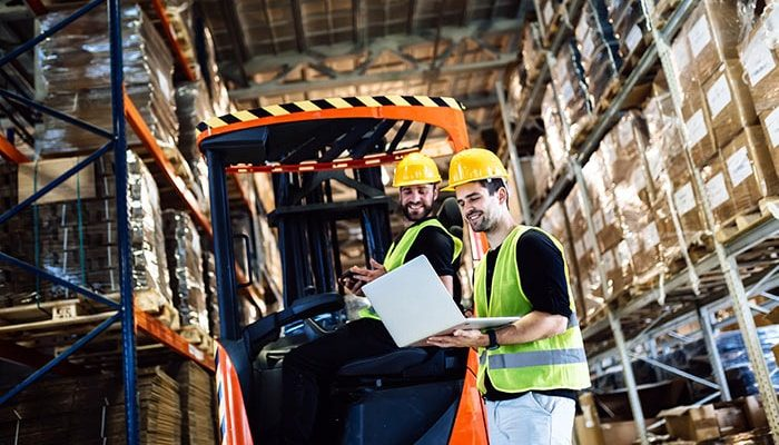 an image of warehouse workers using epicor quick ship on a laptop in the warehouse